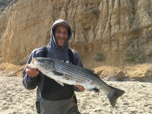 S.W.A.T. team member Mikey of Santa Barbara takes a nice striper from the surf